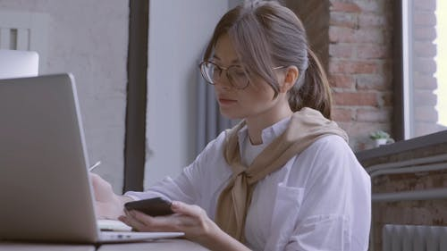 Busy Woman Working With Her Laptop And Smartphone