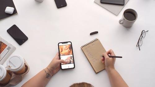 Una Persona Que Toma Notas Mientras Se Desplaza Por Las Fotografías En Un Teléfono Inteligente