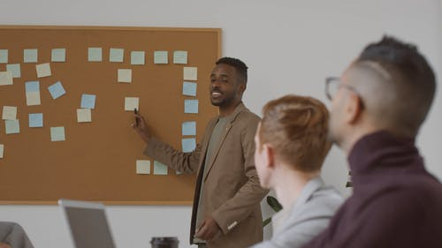 A Man Standing Talking About A Note Stick On The Board