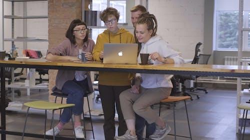 Группа людей, использующих ноутбук во время перерыва на кофе