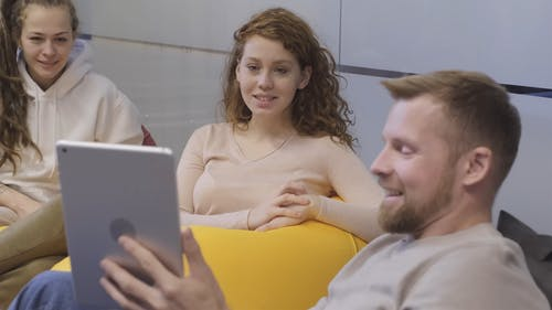 A Man Discussing With Two Women Using A Smart Pad