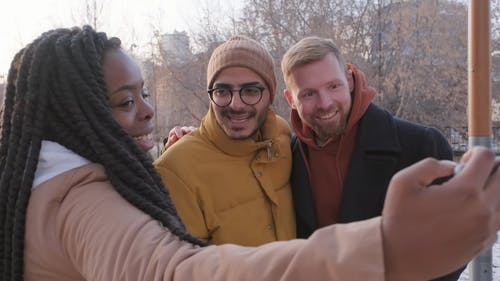 A Woman Taking A Group Selfie Photo Using Her Smartphone