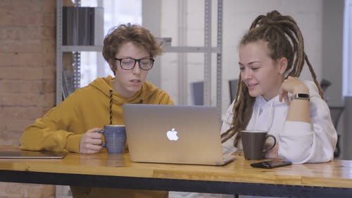 Two Women In Discussion Using A Laptop
