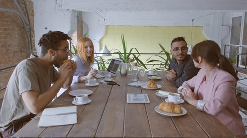 A Group Of People Eating While Working In The Workplace