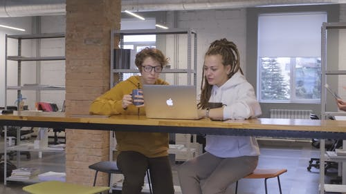 Two People Working With A Laptop