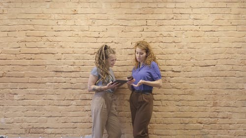 Two Women Standing By A Brick Wall Compares Data Using Their Modern Gadgets