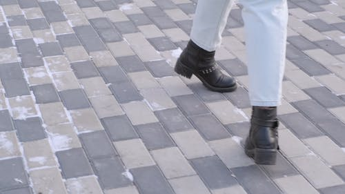 A Person Feet In Leather Shoes Walking On A Concrete Pavement