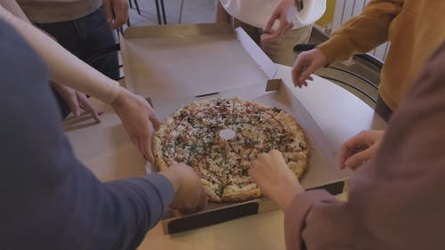Group Of People Grabbing A Slice Of Pizza In The Workplace Pantry