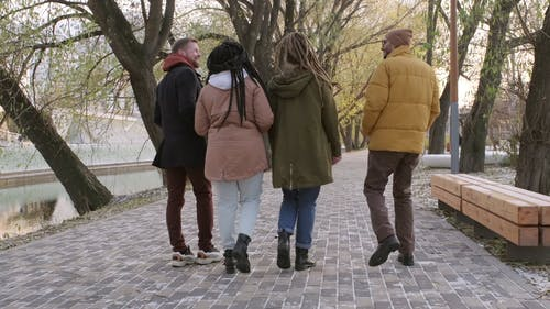 A Group Of People Talking While Walking In A Park