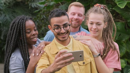 A Group Compressed Position To Take A Group Selfie Photo Using A Smartphone