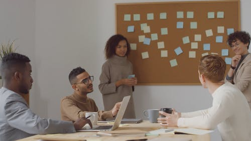 A Group Of People Brainstorming In A Meeting Room And Happily Agreeing With A Handshake On A Plan