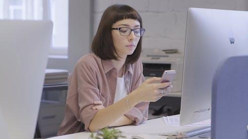 Una Mujer Que Usa Su Teléfono Celular Mientras Está Sentado Frente A Una Computadora