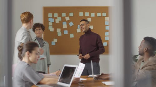 A Man Passing A Smart Pad With Data On Screen To Another Man In A Meeting