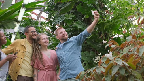 A Group Of People Taking A Group Selfie Photo Inside The Greenhouse Using A Cellphone