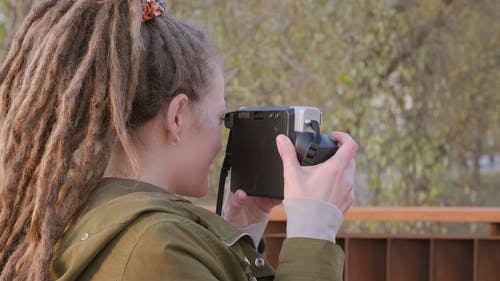 a Woman Taking A Photo Of A Group Using A Modern Camera With Instant Film