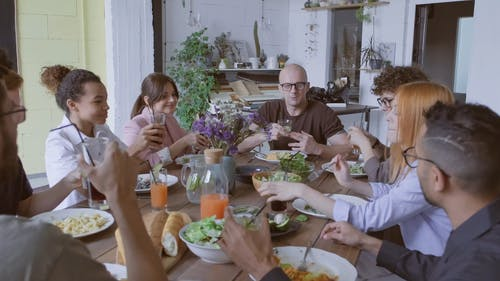 A Group Of People Having A Working Lunch Over A Wooden Table