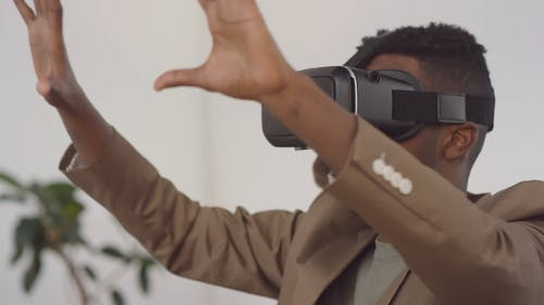 A Man Wearing A Virtually Reality Gear Gesturing With His Hands