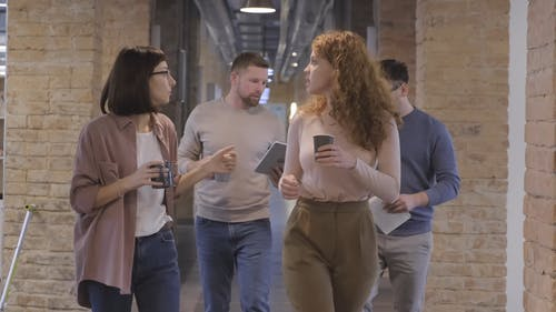 People Walking In The Corridor With Coffee While Having  A  Break