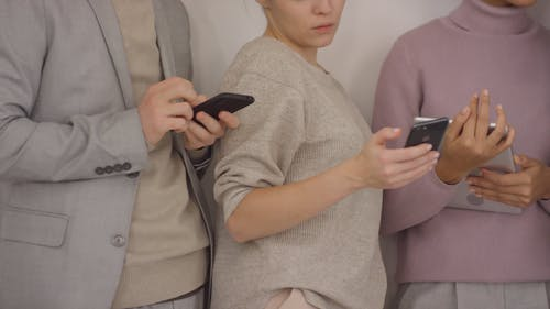 A Group Of People Standing Next To Each Other Are Busy Using Electronic Gadgets