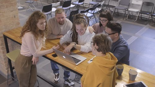 A Group Gathering On A Counter Table Looking At A Laptop