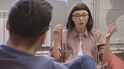A Woman Talking To A Man With Hand Gesture For Emphasis