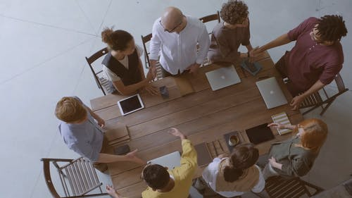 Group Of People Standing Around The Conference Table Greeting Each Other