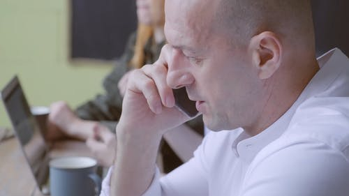 Close-up Of A Man Talking Privately On His Cellphone