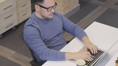 A Man Busy Using A Laptop In His Workplace