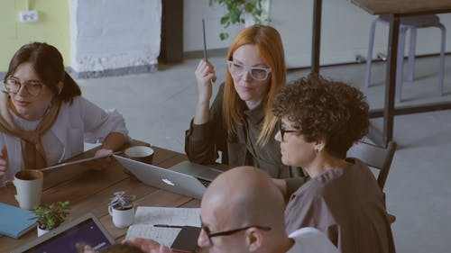 A Group Of People In Discussion At A Business Meeting