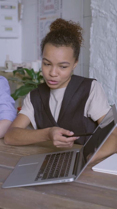 A Woman Discussing Something On A Laptop