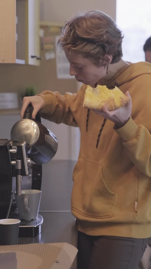 A Woman Eating Pizza While Poring Hot Water On A Cup