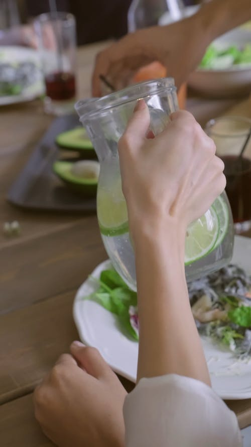 A Woman Pouring Lemonade On Glasses Of People She Is Eating With
