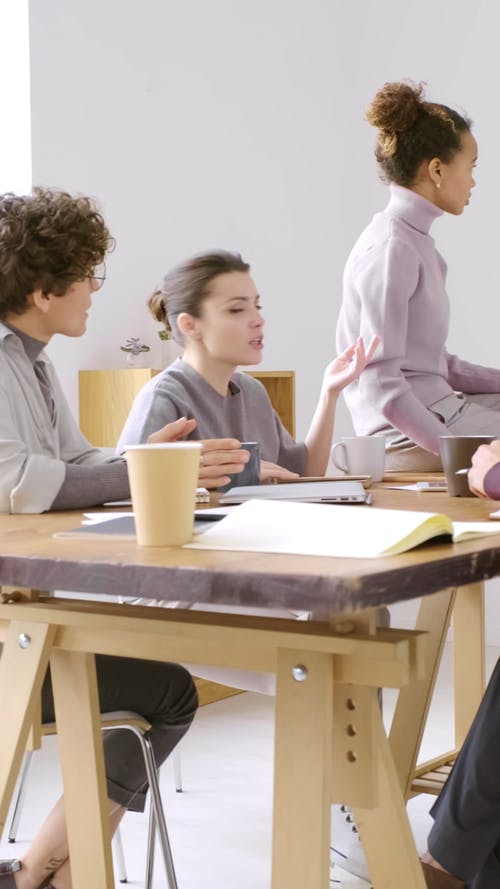 A Group Of People Having A Discussion In A Meeting