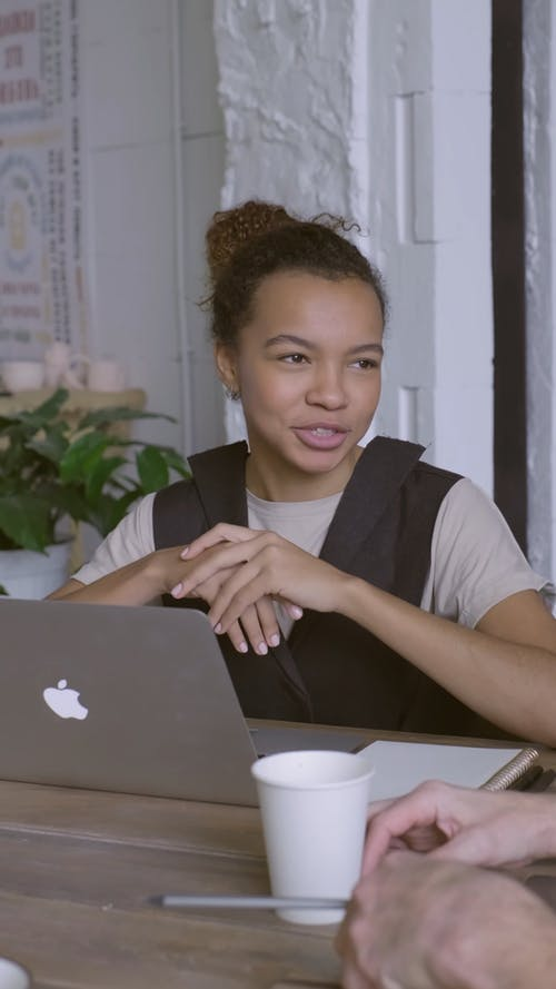 A Woman Sitting In Front Of A Lap Top Speaking To Other People Around