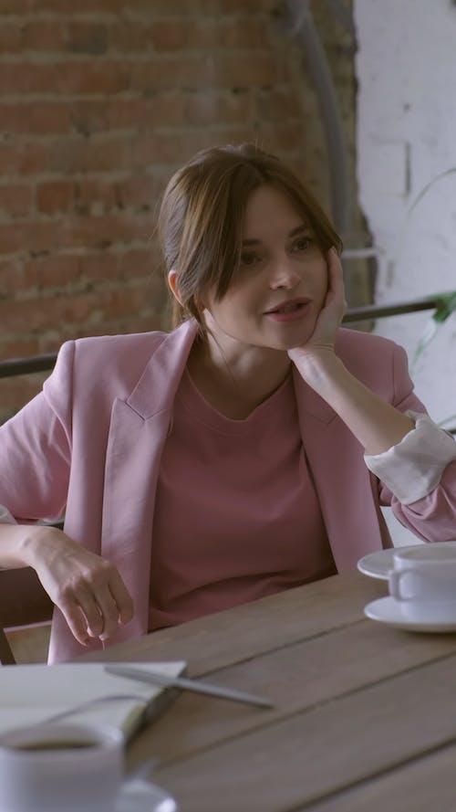 대화 중에 식사를하는 나무 테이블에 앉아있는 여자