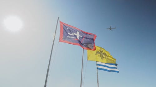 Three Flags Swaying By The Wind On Its Flagpoles