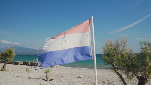 View Of A Beach With Flag Near The Shore