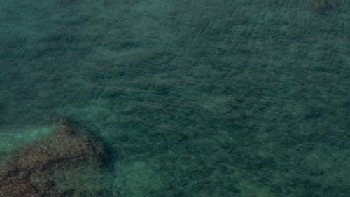 Aerial Footage Of The Sea Surface With Rocks Visible On The Sea Floor