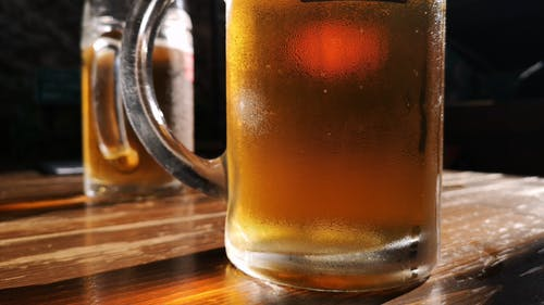 A Mug Of Cold Draft Beers On Top Of A Table