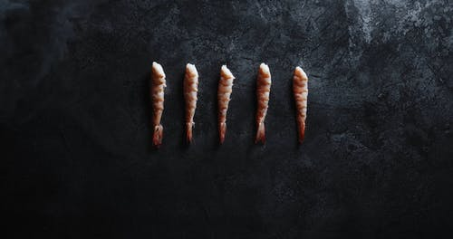 Placing A Sushi Knife On The Table Top Beneath A Line Of Cooked Shrimp