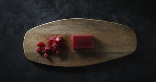 Placing The Sushi Knife Besides Dices And Meat Of Tuna Over A Wooden Chopping Board