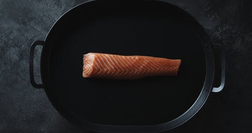 Torching A Slab Of Salmon Meat Over A Sizzling Tray