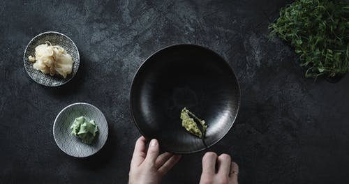 Spreading Green Paste On A Bowl As Based For A Dish