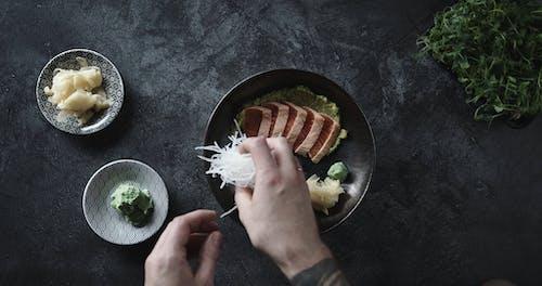 A Chef Adding Shredded Radish In The Plating Of Salmon Cut Sashimi