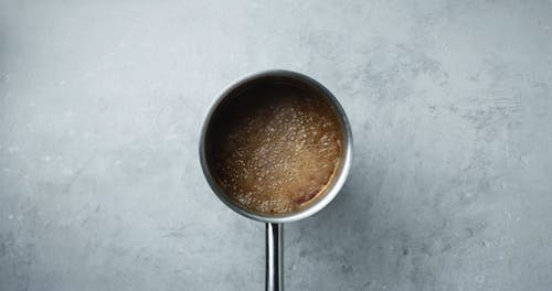 Mixing A Spoonful Of Cream With A Boiling Soup Broth