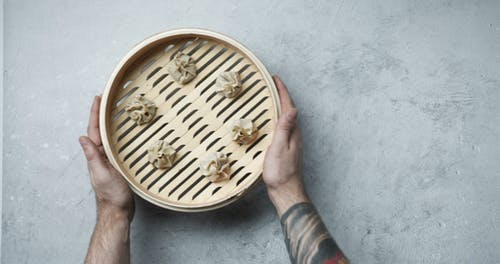 Grabbing The Bamboo Steamer With Raw Dim Sum For Cooking