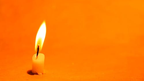 Flame Of A Burning Candle Wick Sways By The Blowing Wind