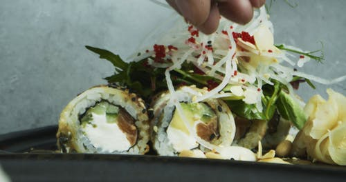 A Chef Sprinkle Sesame Seeds On The Plating Of Sushi Rolls