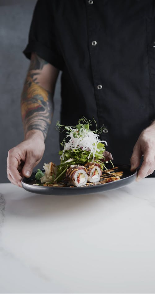 A Chef Prepares A Sushi Rice Roll Fusion With Vegetable Toppings