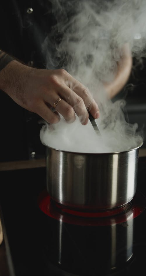 A Chef Preparing Then Tasting The Hot Broth For A Dish